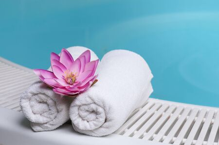 Beautiful lotus flower on towels at the edge of a pool at spa beauty club photo