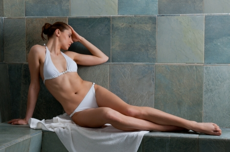 Beautiful young woman relaxing in a Turkish bath at spa photo
