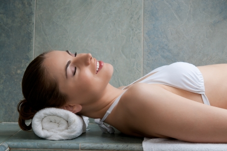 Happy smiling young lady relaxing in a turkish bath at spa center photo
