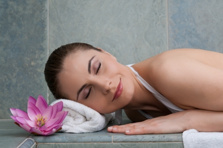 Smiling young beautiful lady relaxing at turkish bath at spa photo