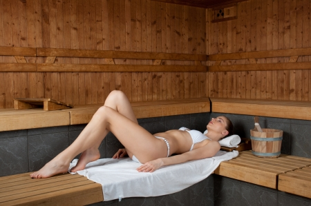 Beautiful young lady lying on a wooden bench in a sauna photo