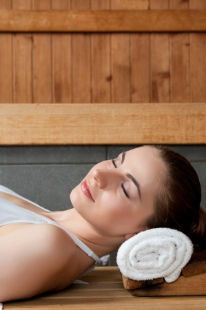 Closeup of beautiful lady relaxing at sauna in a spa center photo