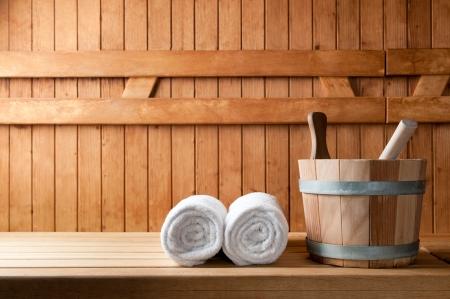 Detail van emmer en witte handdoeken in de sauna