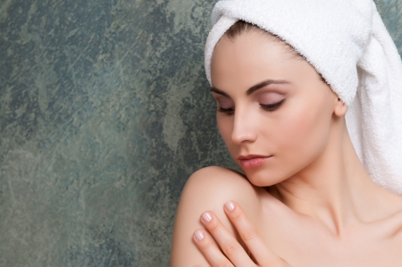 Beautiful young woman touching her soft skin after a beauty treatment Stock Photo - 13741938