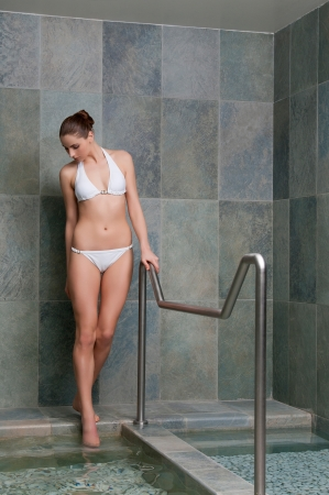 Beautiful young lady walking through water pools for kneipp treatment photo