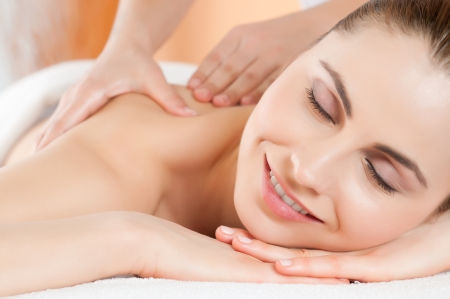 Beautiful young woman receiving hand massage on her back at beauty spa salon photo
