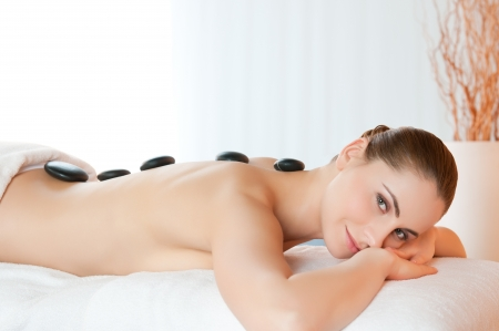 Happy smiling young woman lying with stones on back at beauty spa center photo