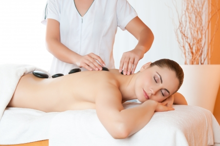 Positioning warm stones on back for lastone therapy at spa center Stock Photo - 14272876