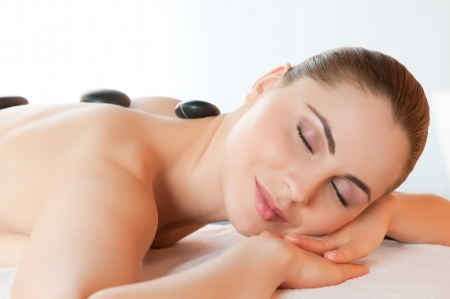 Beautiful young girl relaxing with hot stones on back for a therapy at spa photo