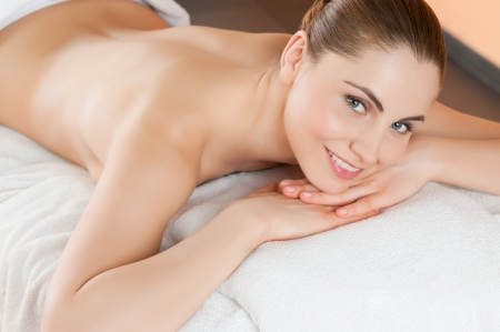 Beautiful young woman lying and relaxing at beauty spa center photo