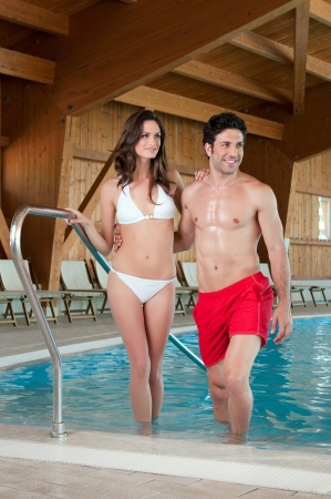 Smiling healthy couple coming out from a swimming pool at spa centre photo