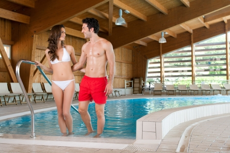 Happy smiling couple enjoy together a thermal pool in a spa centre  photo