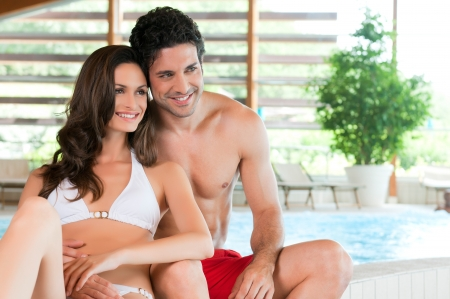 Beautiful young couple relaxing together at the edge of a swimmingpool at spa centre photo