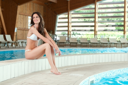 wellness center: Beautiful smiling woman relaxing at the edge of a swimming pool at spa centre Stock Photo