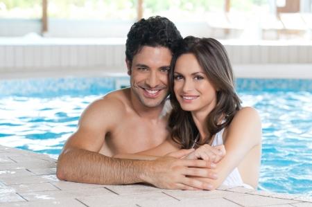 nuoto: Felice coppia sorridente guardando la fotocamera mentre vi rilassate sul bordo di una piscina