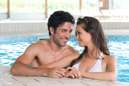 Happy smiling couple relaxing together in a pool at health spa club photo