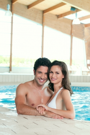 Beautiful young happy couple enjoy a pool at spa centre photo