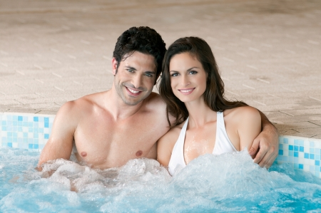 Smiling loving couple relaxing together on a jacuzzi pool at spa photo