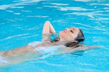 Schöne junge Frau liegt entspannt auf dem Wasser am Pool