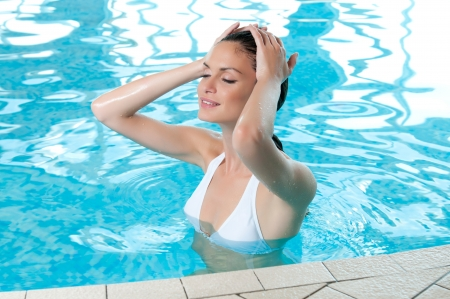 Beautiful young woman refreshing at summer swimming pool photo