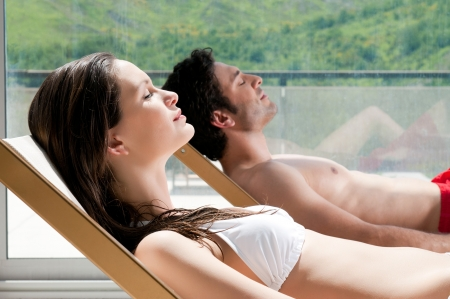 sunbed: Young couple sunbathing together on deck chairs