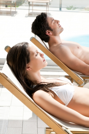 sunbed: Relaxed couple sunbathing together at swimming pool in summer Stock Photo