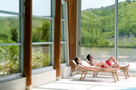 Young couple relaxing and sunbathing together in a beautiful spa centre photo