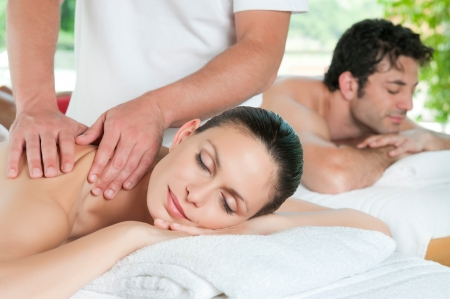 Beautiful young couple enjoy together a massage at spa centre Stock Photo