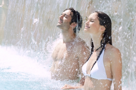 Young couple enjoy together waterfall freshness in a swimmingpool photo