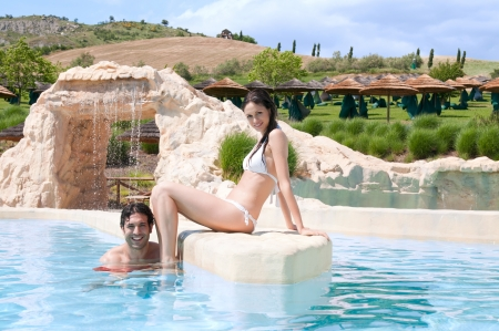 Happy smiling young couple relaxing in the swimmingpool of a resort photo