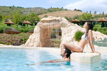 Beautiful young couple relaxing together in the swimmingpool of a resort Stock Photo - 14525856
