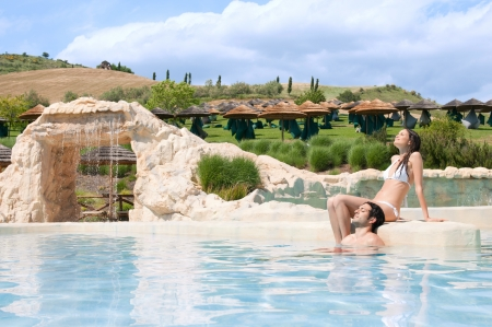 Beautiful young couple relaxing together in the pool of a resort photo