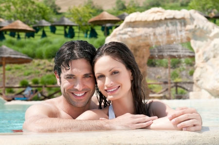 Happy smiling couple enjoy together the freshness of a resort pool photo