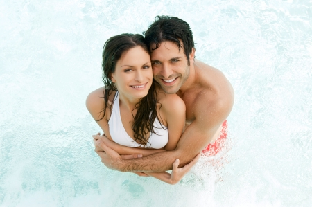 High view of a smiling couple embracing together in the water at summer photo