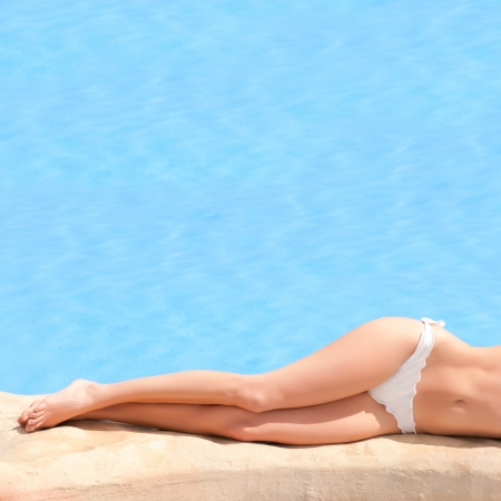 Beautiful young girl lying at water side in summer photo