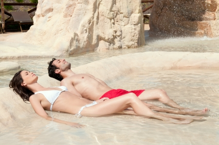 Beautiful young couple sunbathing together at the edge of a swimming pool photo