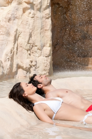 Beautiful young couple relax together at the edge of a swimmingpool at spa centre photo