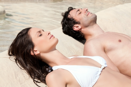 Beautiful young couple sunbathing together in summer photo