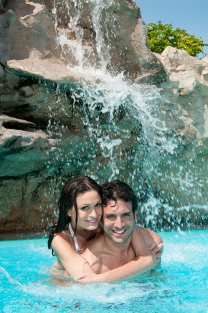 Beautiful young couple enjoy together the summer under the waterfall of a swimming pool photo
