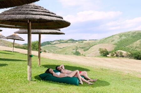 Happy smiling young couple relaxing together on the grass in the nature Stock Photo - 14525862