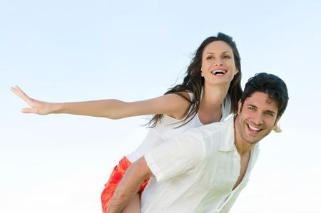 man carrying woman: Happy joyful couple enjoy the freedom of the summer Stock Photo