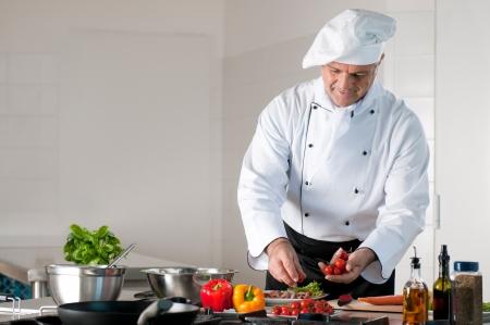 šéfkuchař: Šťastný úsměv zralé kuchař připravuje jídlo s různými zeleninou Reklamní fotografie