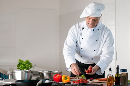 Happy lachende volwassen chef-kok bereiden van een maaltijd met diverse groenten