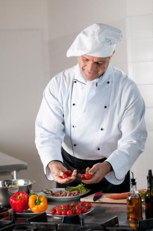 cooking chef: Cocinero Hombre maduro selecciona cuidadosamente los tomates cherry para la preparaci�n de la cena en el restaurante
