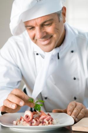 vegetable cook: Happy sorridente guarnire cuoco una insalata di polpo con una foglia di prezzemolo al ristorante