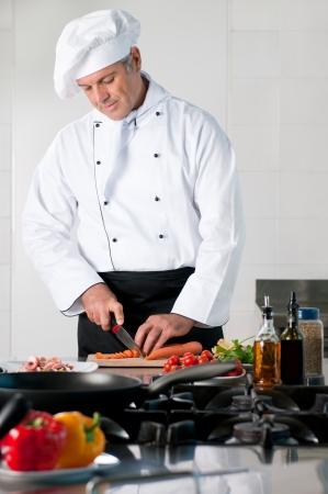 hombre cocinando: Cocinero maduro zanahoria de corte en cocina del restaurante