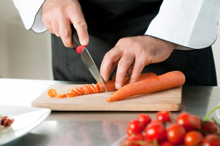 meal preparation: Cutting carrot on a wooden board for meal preparation at restaurant Stock Photo