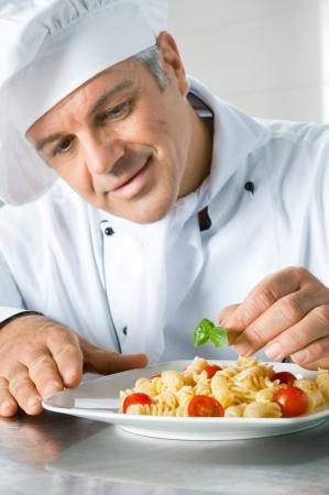 vegetable cook: Felice sorridente cuoco guarnire un piatto di pasta italiana con foglie di basilico