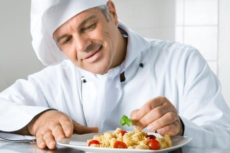 šéfkuchař: S úsměvem zralé šéfkuchař připravuje italské jídlo z těstovin s uspokojením