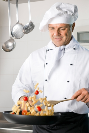 chefs: Happy mature chef stir-fry Italian pasta on a cooking pan at restaurant